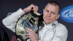 Welterweight UFC champion Georges St-Pierre put his belt on his shoulder during a news conference in Montreal on January 23, 2013. THE CANADIAN PRESS/Paul Chiasson