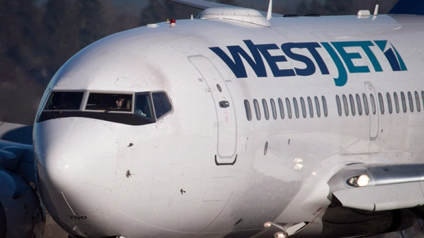 A pilot taxis a Westjet Boeing 737-700 plane to a gate after arriving at Vancouver International Airport on February 3, 2014. THE CANADIAN PRESS/Darryl Dyck