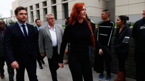 Tree Paine, right, publicist for pop singer Taylor Swift, leads the singer's bother, Austin, into the federal courthouse for the morning session of the the fourth day of a civil trial to determine whether a Denver radio host groped the singer in a case in federal court Thursday, Aug. 10, 2017, in Denver. Former DJ David Mueller sued Swift after she said he touched her backside before a concert in Denver in 2013. He's seeking at least $3 million. Swift countersued for sexual assault and is seeking $1.  (AP Photo/David Zalubowski)