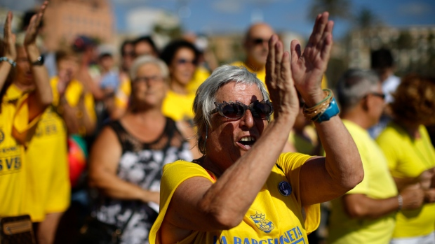 A woman applauds during a protest against tourism in Barcelona, Spain, Saturday, Aug. 12, 2017. The residents claim that the influx of tourists has increased the price of rents and produced a spike in rowdy behavior by party-seeking foreigners. The protest comes amid growing tension between governmental authorities and radical leftist groups after they launched a campaign of vandalism against mass tourism in Barcelona and other parts of Spain. (AP Photo/Manu Fernandez)
