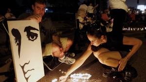 This Aug. 15, 2010 file photo shows Melanie Curry as she lights candles at an Elvis Presley display she made with Judd Cannon, left, on Elvis Presley Boulevard in front of Graceland, Presley's Memphis, Tenn. home. Friends and fans of late singer and actor Elvis Presley are descending on Memphis, Tennessee, for Elvis Week, the annual celebration of his life and career. It coincides with the 40th anniversary of the passing of Presley, who died on Aug. 16, 1977. (AP Photo/Mark Humphrey, File)