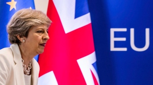FILE- In this Friday, June 23, 2017 file photo British Prime Minister Theresa May prepares to address a media conference at an EU summit in Brussels. May's office said on Monday, July 31, 2017 that free movement to Britain from European Union countries will end when the U.K. leaves the bloc in March 2019, but it's uncertain what migration arrangements will look like after that. (AP Photo/Geert Vanden Wijngaert, file)