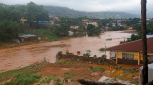 A torrent of water flows through a flooded neighbourhood in Regent, east of Freetown, Sierra Leone Monday, Aug. 14 , 2017. (AP Photo/ Manika Kamara)