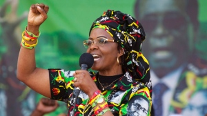 FILE -- In this July 29, 2017 file photo Zimbabwe's first lady, Grace Mugabe, greets supporters at a rally in Zimbabwe. South Africa's police minister says the wife of Zimbabwe's president, background image, has handed herself over to police after being accused of assaulting a young woman Sunday night. (AP Photo/Tsvangirayi Mukwazhi, File)