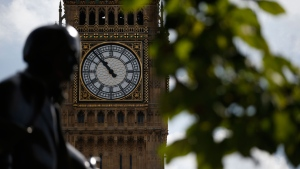 The statue of former British Prime Minister David Lloyd George is silhouetted against the Queen Elizabeth Tower which holds the bell known as 'Big Ben' in London, Monday, Aug. 14, 2017. (AP Photo/Alastair Grant)