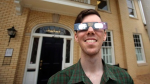 Library Assistant Trey Ross wears eclipse glasses outside Mauney Memorial Library in Kings Mountain, N.C., Wednesday, Aug. 2, 2017. Glasses are being given away at the library for free while supplies last ahead of the big event on August 21. (Brittany Randolph/The Star via AP)