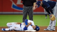 Toronto Blue Jays shortstop Ryan Goins (17) lies in pain after being tagged out and stepped on by Tampa Bay Rays shortstop Daniel Robertson (29) during sixth inning AL baseball action in Toronto on Wednesday, August 16, 2017. THE CANADIAN PRESS/Nathan Denette