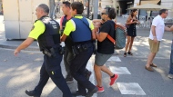 An injured person is carried in Barcelona, Spain, Thursday, Aug. 17, 2017 after a white van jumped the sidewalk in the historic Las Ramblas district, crashing into a summer crowd of residents and tourists and injuring several people, police said. (AP Photo/Oriol Duran)