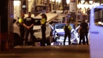 Police officers stand next to the van involved on an attack in Las Ramblas in Barcelona, Spain, Thursday, Aug. 17, 2017. A white van jumped up onto a sidewalk and sped down a pedestrian zone Thursday in Barcelona's historic Las Ramblas district, swerving from side to side as it plowed into tourists and residents. Police said 13 people were killed and more than 50 wounded in what they called a terror attack. (AP Photo/Manu Fernandez)