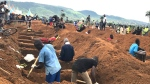 Volunteers prepare graves during a mass funeral for victims of heavy flooding and mudslides in Regent at a cemetery in Freetown, Sierra Leone, Thursday, Aug. 17, 2017. The government has begun burying the hundreds of people killed earlier this week in mudslides in Sierra Leone's capital, and it warned Thursday of new danger from a large crack that has opened on a mountainside where residents were told to evacuate. (AP Photo/ Manika Kamara)