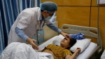 Doctor Vu Minh Dien, left, examines dengue patient Tran Thi Xuyen at the National Hospital of Tropical Diseases in Hanoi, Vietnam, Friday, Aug. 18, 2017. Vietnam has been battling raging dengue fever outbreaks with more than 10,000 new infections reported over the past week stretching its medical system. (AP Photo/Tran Van Minh)