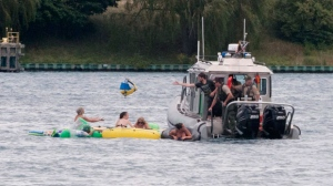 A Customs and Border Protection boat helps floaters during Float Down on the St. Clair River in Port Huron, Mich., Sunday, Aug. 21, 2016. The west winds blew most boaters toward the Canada shore and they had to be pulled back to the U.S. Thousands were expected to take part in Port Huron Float Down. (Mark R. Rummel/The Times Herald via AP)