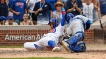 Chicago Cubs' Javier Baez, left, scores as Toronto Blue Jays' Raffy Lopez, right, applies a late tag during the 10th inning of a baseball game, Sunday, Aug. 20, 2017, in Chicago. The Cubs won 6-5. (AP Photo/Kamil Krzaczynski)