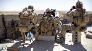 Belgian special forces soldiers sit on a rooftop with a guided-missile launcher, a few miles from the frontline, in the village of Abu Ghaddur, east of Tal Afar, Iraq, Sunday, Aug. 20, 2017. (AP Photo/Balint Szlanko)