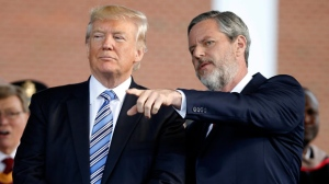 In this May 13, 2017 photo, President Donald Trump stands with Liberty University President Jerry Falwell Jr. in Lynchburg, Va. Falwell, in tweets and interviews in recent days, defended the president's response to a white nationalist rally in Charlottesville, Virginia, that descended into deadly violence. A small group of Liberty University graduates are planning to return their diplomas to the evangelical Virginia school as a rebuke of Falwell Jr.'s latest showing of unwavering support for Donald Trump. (AP Photo/Steve Helber)