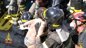 Firefighters pull out a boy, Mattias, from the collapsed building in Casamicciola, on the island of Ischia, near Naples, Italy, a day after a 4.0-magnitude quake hit the Italian resort island, Tuesday, Aug. 22, 2017. irefighters freed a 7-month-old baby and an older brother from rubble of a house some seven hours after the quake, and are continuing work on rescuing another brother who remained trapped. (Italian Firefighters Vigili del Fuoco via AP)
