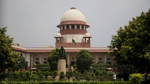 A gardener works in the lawns of the Supreme Court in New Delhi, India, Tuesday, Aug. 22, 2017. India's Supreme Court said Tuesday that the Muslim practice that allows men to instantly divorce their wives is unconstitutional and requested the government legislate an end to the practice. (AP Photo/Altaf Qadri)
