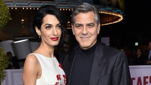 """FILE - In this Feb. 1, 2016, file photo, Amal Clooney, left, and George Clooney arrive at the world premiere of """"Hail, Caesar!"""" in Los Angeles. The couple announced Tuesday, Aug. 22, 2017, that their Clooney Foundation for Justice is supporting the Southern Poverty Law Center with a $1 million grant to combat hate groups in the United States. (Photo by Jordan Strauss/Invision/AP, File)"""