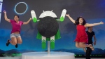 Sisters Courtney, left, and Ashley Chang pose for photos with friends next to the newly-unveiled sculpture of the Android 8.0 Oreo operating system, Monday, Aug. 21, 2017, in New York. Oreo boasts several new features, including the ability to respond to notifications directly on a phone's home screen and the ability to access apps without installing them on a device. (AP Photo/Mark Lennihan)