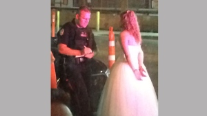 A bride in handcuffs speaks with a police officer following a brawl at an Edmonton bar. (@IAmByks /Twitter)