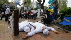 In this May 1, 2016 file photo, members of Banolim, an advocacy group for workers in the electronic industry, perform during a rally against Samsung's response to the former company employees' health problems on the street in Seoul, South Korea. (AP Photo/Ahn Young-joon, File)