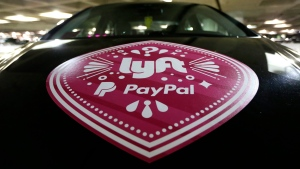 In this March 31, 2016, a Lyft ride-hailing service logo is displayed on a vehicle at Seattle-Tacoma International Airport in Seattle. (AP / Ted S. Warren)