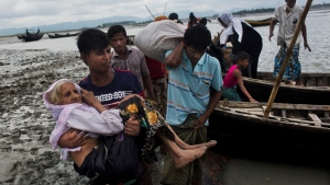 A Rohingya ethnic minority from Myanmar carries an elderly woman as they alight from a local boat on which they crossed a river, after crossing over to the Bangladesh side of the border near Cox's Bazar's Dakhinpara area, Saturday, Sept. 2, 2017. (AP Photo/Bernat Armangue)