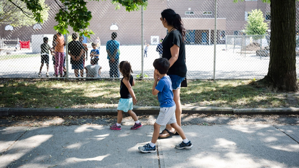 Serina Manek is seen in her Leslieville neighbourhood in Toronto with her two children Zane (5) and Mia (3) Partridge on Wednesday, August 30, 2017. Manek says that the increase in condo development has not only made student placement in local schools more difficult, but traffic through local streets and alleyways have also increased. The Canadian Press/Christopher Katsarov