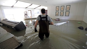 Gaston Kirby walks through floodwater inside his home in the aftermath of Hurricane Harvey, Monday, Sept. 4, 2017, near the Addicks and Barker Reservoirs, in Houston. (AP Photo / David J. Phillip)