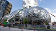 "In this April 27, 2017 file photo, construction continues on three large, glass-covered domes as part of an expansion of the Amazon.com campus in downtown Seattle. Amazon said Thursday, Sept. 7, that it will spend more than $5 billion to build another headquarters in North America to house as many as 50,000 employees. It plans to stay in its sprawling Seattle headquarters and the new space will be ""a full equal"" of its current home, said founder and CEO Jeff Bezos. (AP Photo/Elaine Thompson)"