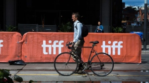 A pedestrian walks by TIFF signs at the Toronto International Film Festival on Thursday, Sept. 7, 2017. THE CANADIAN PRESS/Chris Donovan