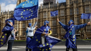 Pro-remain supporters of Britain staying in the EU, wear EU flag masks as they take part in an anti-Brexit protest outside the Houses of Parliament in London, Monday, Sept. 11, 2017.  (AP Photo/Matt Dunham)