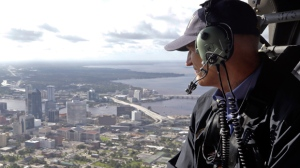 Gov. Rick Scott flies over Jacksonville, Fla., in a military helicopter as he looks at damage to the downtown area during the aftermath of Hurricane Irma on Tuesday, Sept. 12, 2017. (AP Photo/John Raoux)