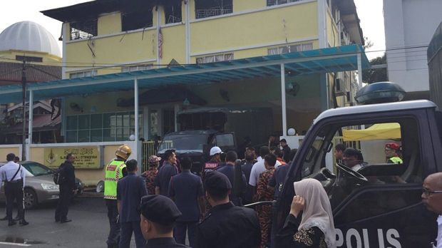 In this photo provided by @FRIENDOFBOMB, police prepare to bring victims out of an Islamic religious school after a fire on the outskirts of Kuala Lumpur, Malaysia, Thursday, Sept. 14, 2017. A fire department official in Malaysia said the fire at the school killed people, mostly teenagers. (@FRIENDOFBOMBA via AP)