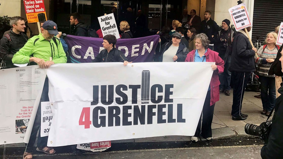 """Protesters outside the Grenfell Tower public inquiry in central London where Sir Martin Moore-Bick is delivering his opening statement during its first preliminary hearing, Thursday, Sept. 14, 2017. The head of a government-ordered inquiry into the London tower block fire that killed at least 80 people has acknowledged that survivors feel a """"great sense of anger and betrayal."""" (Jack Hardy/PA via AP)"""