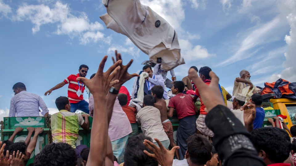 Rohingya Muslim children, who recently crossed over from Myanmar into Bangladesh, reach out to catch clothes thrown toward them by locals near Balukhali refugee camp, Bangladesh, Friday, Sept. 15, 2017. Thousands of Rohingya are continuing to stream across the border, with U.N. officials and others demanding that Myanmar halt what they describe as a campaign of ethnic cleansing that has driven nearly 400,000 Rohingya to flee in the past three weeks. (AP Photo/Dar Yasin)