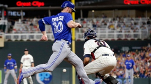 Toronto Blue Jays' Josh Donaldson, left, beats the throw to score on a Justin Smoak hit in the fourth inning of a baseball game against the Minnesota Twins, Saturday, Sept. 16, 2017, in Minneapolis. (AP Photo/Jim Mone)
