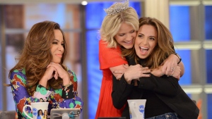 "In this photo provided by American Broadcasting Companies, Inc., Sara Haines, center, embraces Jedediah Bila, right, after Bila announces Monday, Sept. 18, 2017, will be her last day as co-host of ""The View."" Sunny Hostin is sitting at left. (Lorenzo Bevilaqua/ABC via AP)"