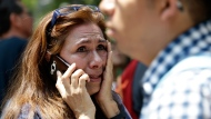 A woman tries to reach people on her cellphone after she evacuated with others to Paseo de la Reforma street after an earthquake in Mexico City, Tuesday, Sept. 19, 2017. A powerful earthquake jolted central Mexico on Tuesday, causing buildings to sway sickeningly in the capital on the anniversary of a 1985 quake that did major damage. (AP Photo/Marco Ugarte)