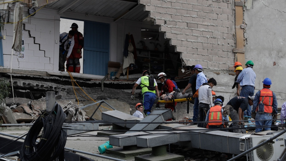 An injured woman is carried out of a building that collapsed during an earthquake in Mexico City, Tuesday, Sept. 19, 2017. A powerful earthquake jolted central Mexico on Tuesday, causing buildings to sway sickeningly in the capital on the anniversary of a 1985 quake that did major damage. (AP Photo/Rebecca Blackwell)