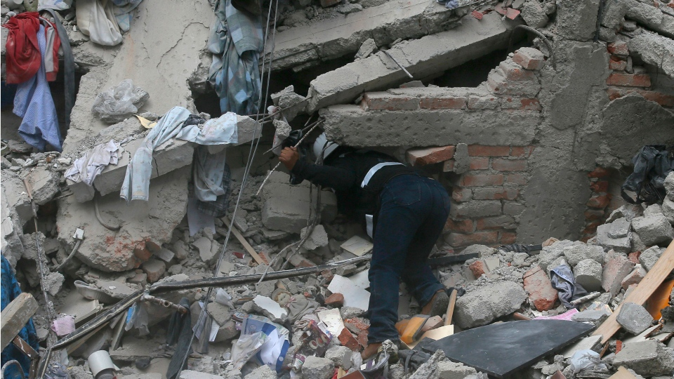 A construction worker searches a building that collapsed after an earthquake, in the Roma neighborhood of Mexico City, Tuesday, Sept. 19, 2017. (AP Photo/Eduardo Verdugo)