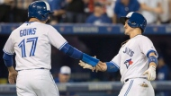 Toronto Blue Jays' Darwin Barney, right, is congratulated by Ryan Goins after driving him in with a two-run home run in the sixth inning of their American League MLB baseball game against the Kansas City Royals in Toronto on Tuesday, September 19, 2017. THE CANADIAN PRESS/Fred Thornhill