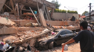 A car lays crushed under the collapsed Enrique Rebsamen school in Mexico City, Tuesday, Sept. 19, 2017. The earthquake stunned central Mexico, killing more than 100 people as buildings collapsed in plumes of dust. (AP Photo/Carlos Cisneros)