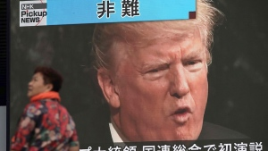 A woman walks past a TV screen showing U.S. President Donald Trump while reporting on his maiden address at the U.N. General Assembly, in Tokyo Wednesday, Sept. 20, 2017. (AP Photo/Eugene Hoshiko)