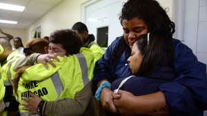 Rescue team members Candida Lozada, left, and Stephanie Rivera, second from left, Mary Rodriguez, left at right side, and Zuly Ruiz, right at right side, merge into a hug desperate to go out to attend several calls for help from citizens in need of assistance during the impact of Maria, a Category 5 hurricane that started to hit the eastern region of the island, in Humacao, Puerto Rico, Tuesday, Sept. 20, 2017. At that point, Maria downgraded to a category 4 hurricane. (AP Photo/Carlos Giusti)