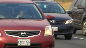A motorist is seen driving with a cell phone in hand in an undated file image.