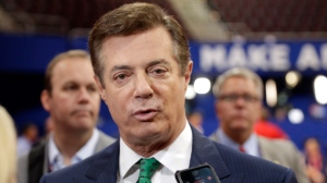 """In this July 17, 2016 file photo, then-Trump Campaign Chairman Paul Manafort talks to reporters on the floor of the Republican National Convention at Quicken Loans Arena in Cleveland as Rick Gates listens at back left. Manafort, said during the presidential race that he was willing to provide """"private briefings"""" for a Russian billionaire the U.S. government considers close to Russian President Vladimir Putin. That's according to a July 2016 email exchange Manafort wrote to a former employee of his political consulting firm about offering to brief Russian billionaire Oleg Deripaska. (AP Photo/Matt Rourke, File)"""