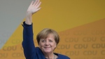 In this photo taken Thursday, Sept. 21, 2017, German Chancellor Angela Merkel waves at a election campaign event of the Christian Democratic Union for Sunday's election in Fritzlar, Germany. Merkel appears all but certain to win a fourth term when Germans vote Sunday after a humdrum campaign produced few divisive issues but saw smaller parties gain support _ including the nationalist, anti-migration Alternative for Germany, which is set to become the most right-wing party in parliament for 60 years. (Swen Pfoertner/dpa via AP)