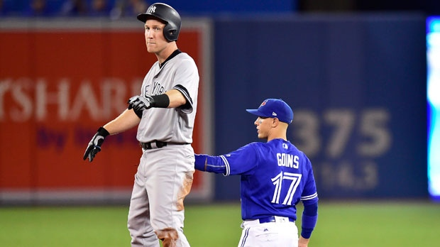 Toronto Blue Jays shortstop Ryan Goins (17) holds the tag on New York Yankees third baseman Todd Frazier (29) after hitting a double during third inning AL baseball action in Toronto on Friday, September 22, 2017. THE CANADIAN PRESS/Frank Gunn