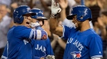 Toronto Blue Jays' Ryan Goins, left, celebrates his grand-slam against the New York Yankees with Kevin Pillar, back, and Teoscar Hernandez, right, in the sixth inning in their American League MLB baseball game in Toronto on Friday, September 22, 2017. THE CANADIAN PRESS/Fred Thornhill